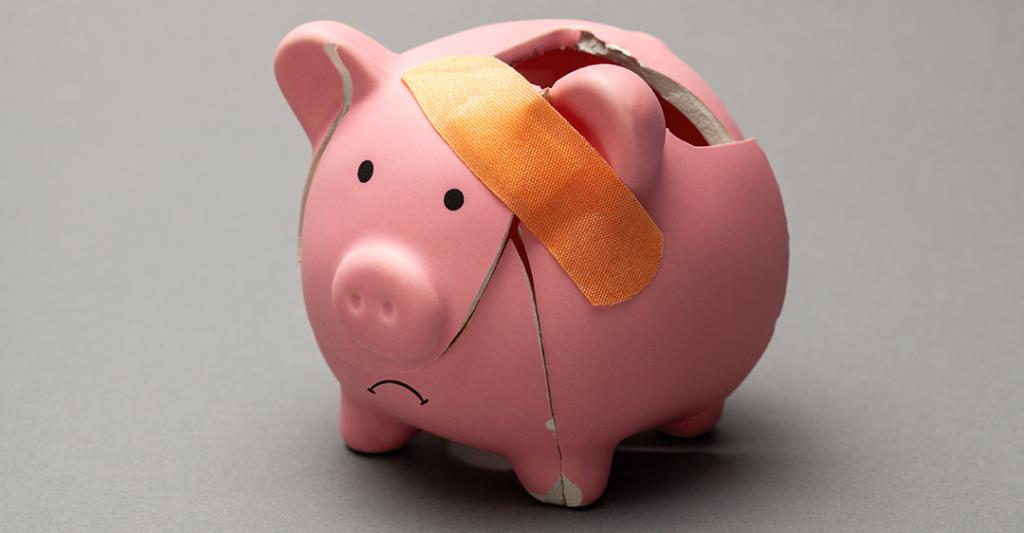 Alcancía en forma de cerdito rosado quebrada, cochinito alcancía, que significa la Ley HEALS para los negocios