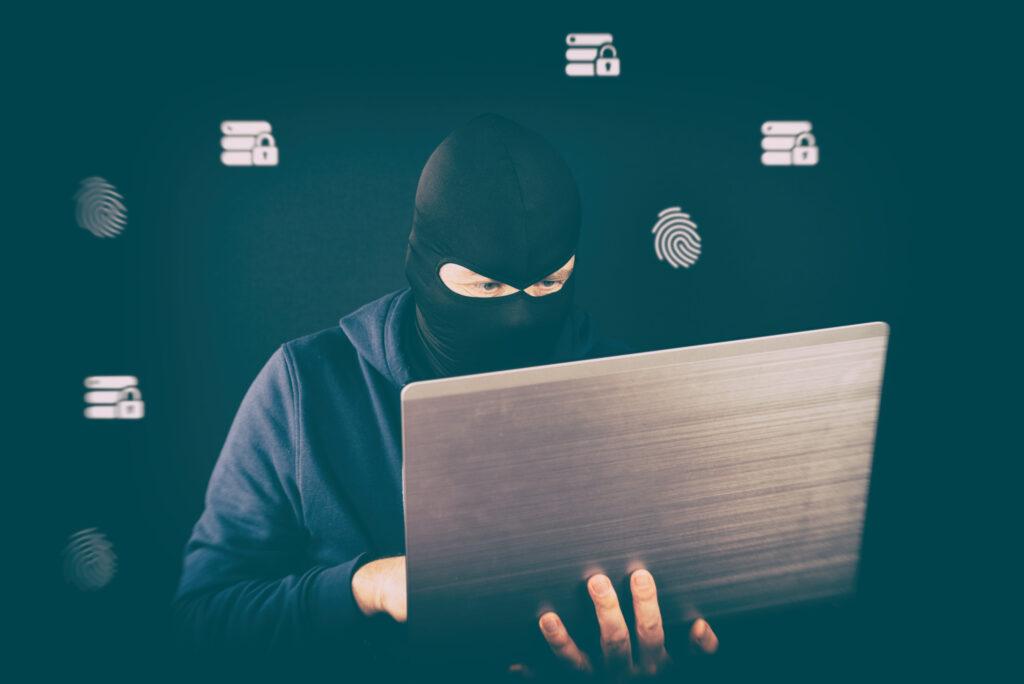 hombre que lleva una máscara negra con ordenador, fraude por correo electrónico, protege su negocio