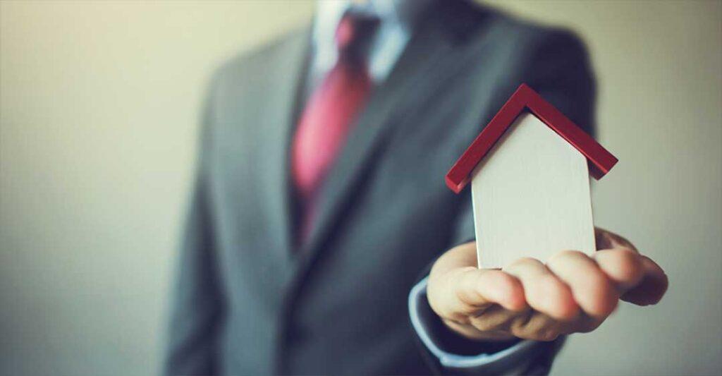 hombre en traje con la mano extendida sosteniendo una casa en miniatura, herencia de propiedad de la Florida, legalización de los bienes en Florida a distancia