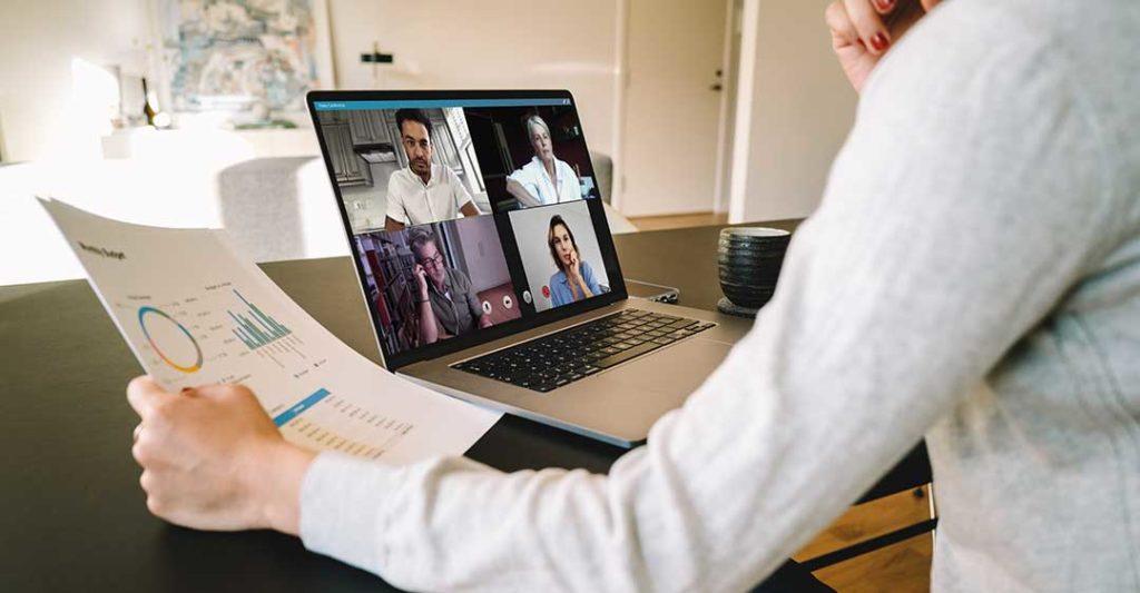 mujer en una videoconferencia en un portátil mirando un informe, trabajando desde las leyes del hogar, leyes de trabajo desde casa