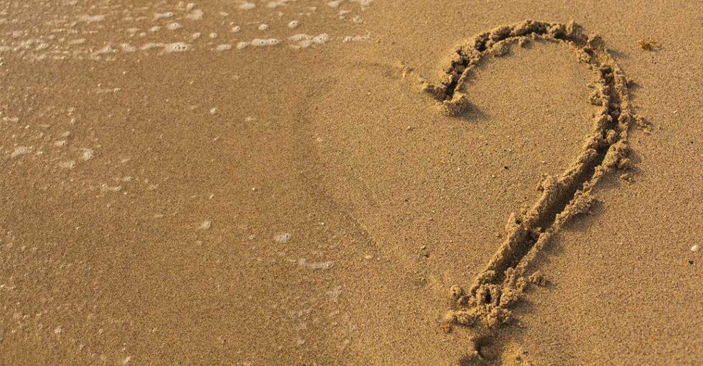 arena en la playa, agua desvaneciendo medio corazón dibujado en la arena, consejos y trucos de separación para expatriados