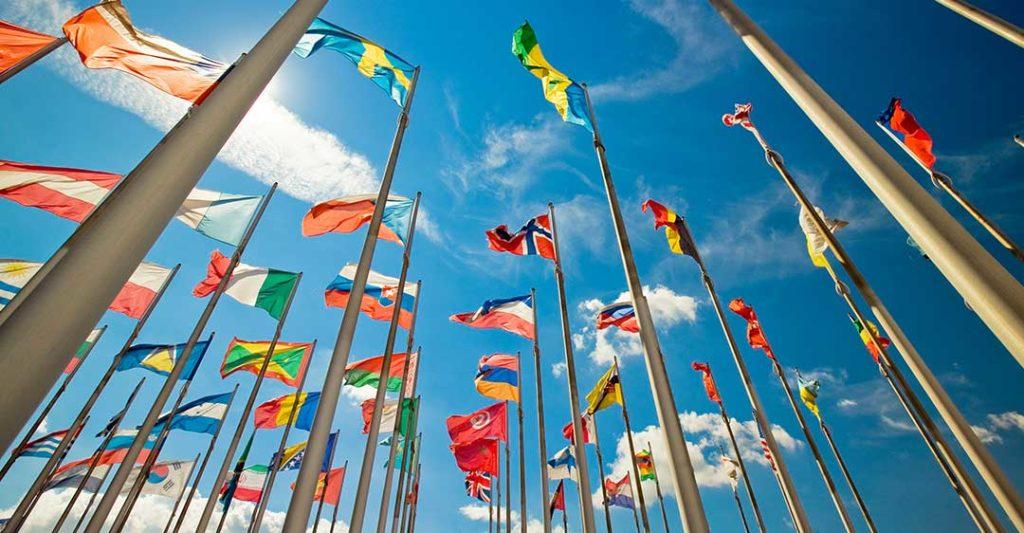 Personas sosteniendo diferentes banderas. Vista posterior. Fondo de cielo soleado, Convención de La Haya, Conferencia de La Haya, Tratado Internacional, iniciativa intergubernamental