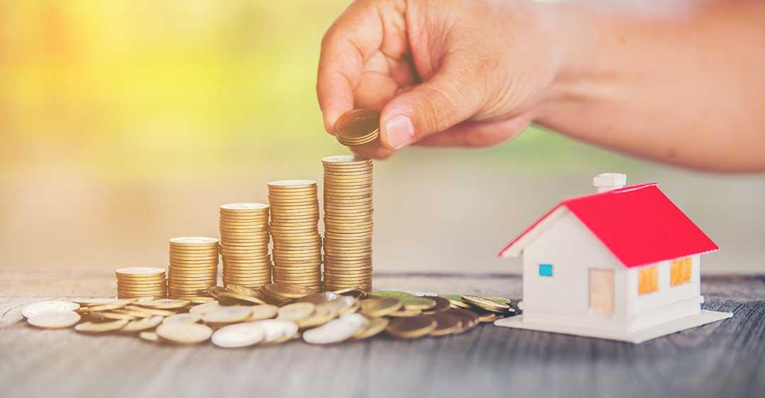 mano de hombre sacando monedas de una pila de monedas, casa modelo, inversión, impuesto de plusvalía, planificación patrimonial,