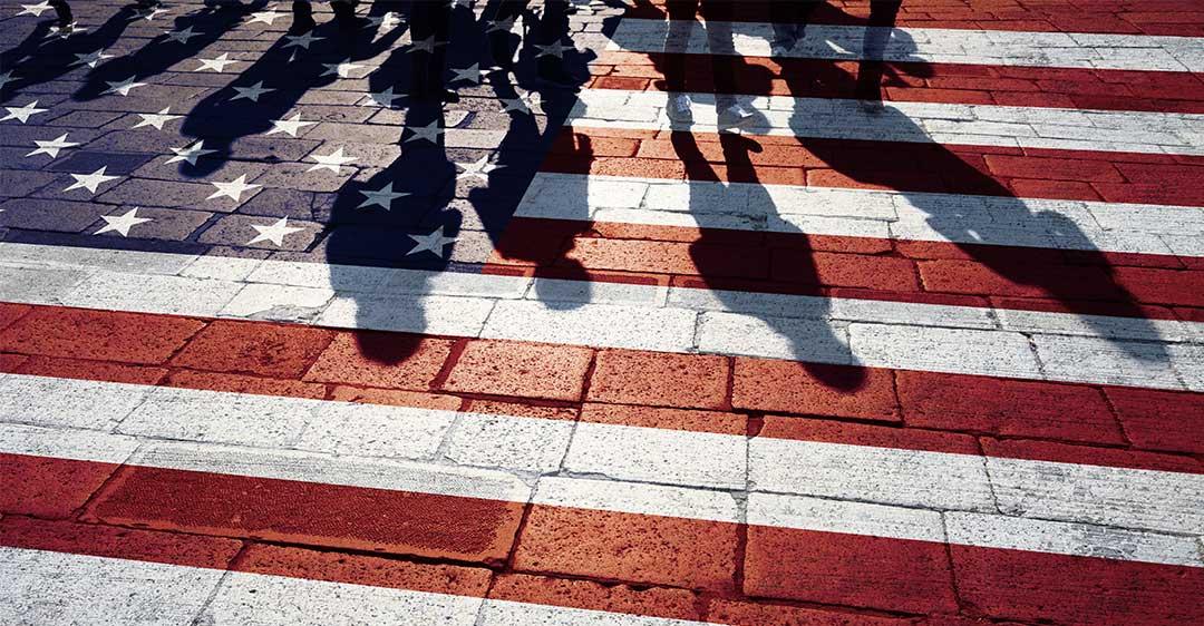 bandera de los EE.UU pintada en una pasarela de ladrillos con sombras de personas caminando, las reglas de inmigración de Biden impactan las empresas, los negocios internacionales,